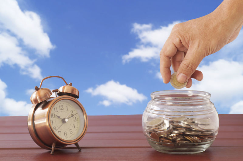 Close-up of hand putting coin in jar with alarm clock on table