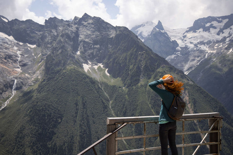 Woman looking at mountains while standing on observation point