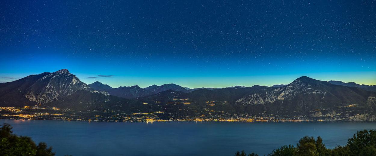 I took this photograph during a warm summer morning (05:30AM) to see the stars and the sunrise over the beautiful mountains of Lake Garda. This photograph contains 15 different photographs and are combined to one massive photograph. Because this one is so massive it's perfect to print it really really big! You can cover you wall with it! That's like the best way to fill your wall right!? Right!? It's huge! Astronomy Backgrounds Blue Glacier Landscape Landscape_Collection Landscape_photography Mountain Mountain Peak Mountain Range Natural Parkland Nature Night Nightphotography No People Outdoors Panorama Scenics Sky Space Summer Tourism Travel Travel Destinations Water EyeEmNewHere