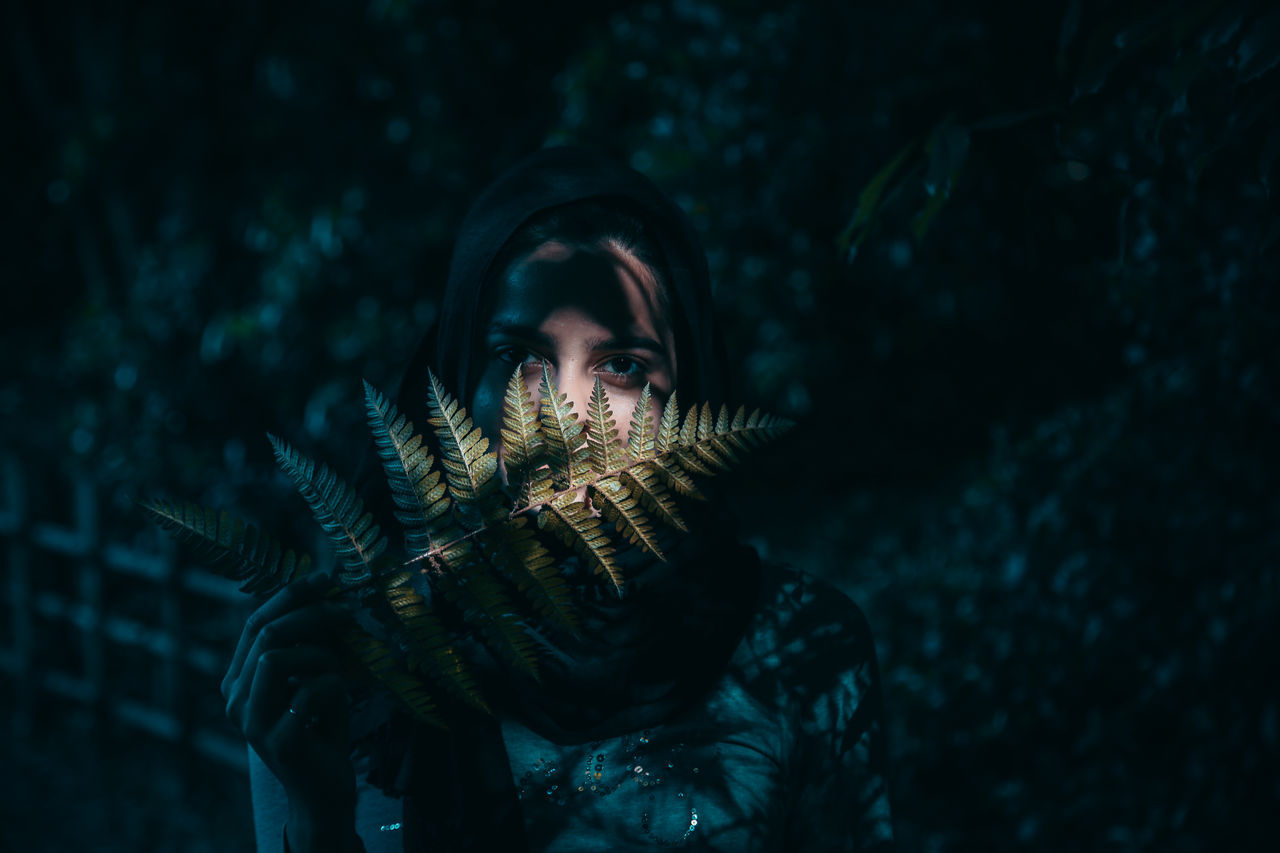 Portrait of young woman holding leaf while standing in park at night