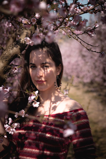 Portrait of a beautiful young woman with cherry blossom