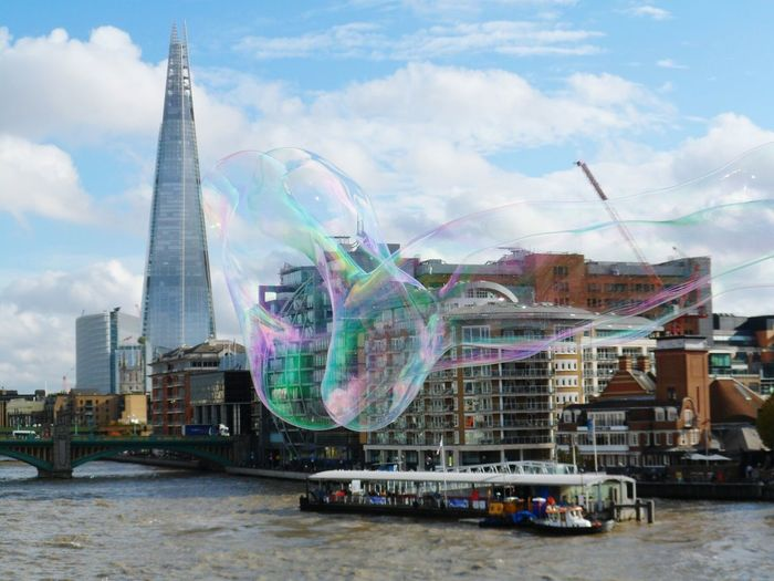 Close-Up Of Bubble Against River And Buildings In City