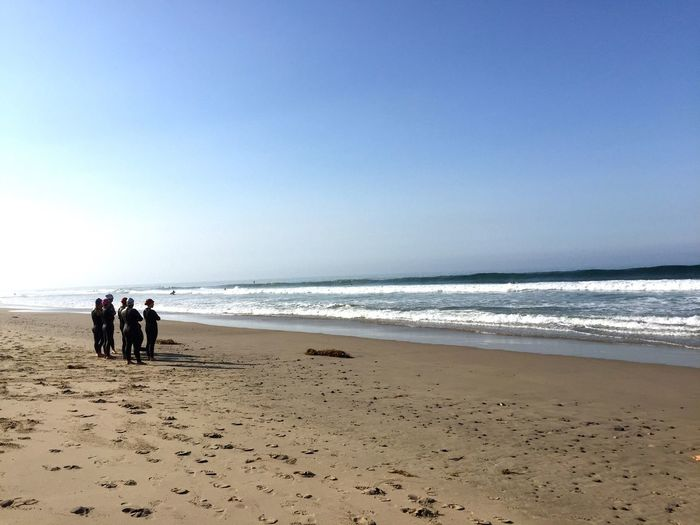 People wearing wetsuit while standing on shore at beach against clear sky