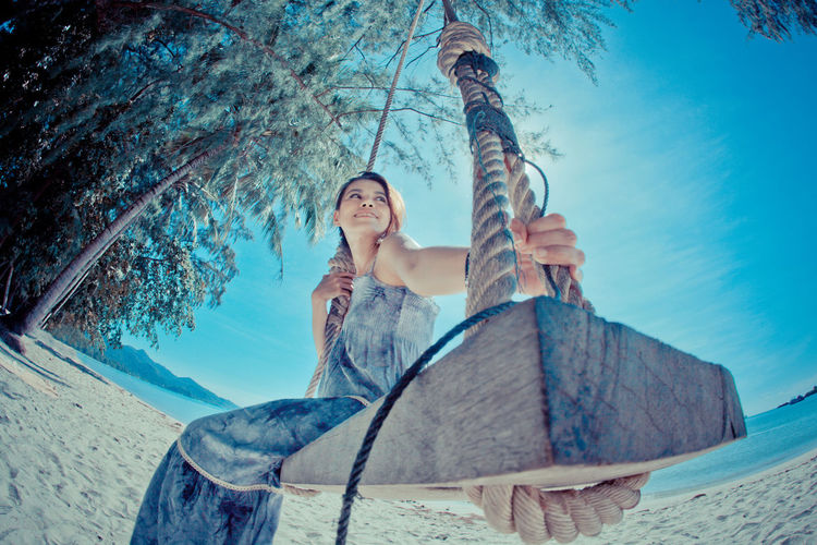 Low angle view of woman sitting on swing at beach