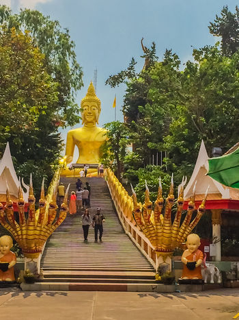 Pattaya, Thailand - January 21, 2016: Beautiful Entrance and steps leading up to the giant Buddha temple in Pattaya, Thailand Big Buddha Naga Pattaya Pattaya Thailand Pattaya, Thailand Architecture Big Buddha Temple Big Buddha, Thailand Built Structure Day Gold Colored Golden Color Human Representation Idol Lifestyles Male Likeness Men Outdoors Pattaya City People Place Of Worship Real People Religion Sculpture Sky Spirituality Statue Travel Destinations Tree