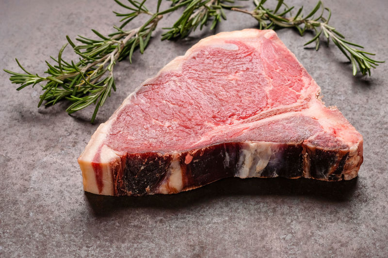 Raw dry aged beef steak with rosemary Backlight Backlit Barbecue Beef Close-up Comfort Food Dry Age Ribeye Dry Aged Dry Aged Beef Fillet Food Food And Drink Freshness Indoors  Meat No People Preparation  Raw Food Rib Roast Dinner Roasted Rosemary SLICE Steak T-bone Steak