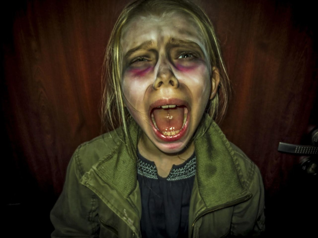 Close-Up Of Girl With Spooky Make-Up Screaming While Standing Against Door During Halloween