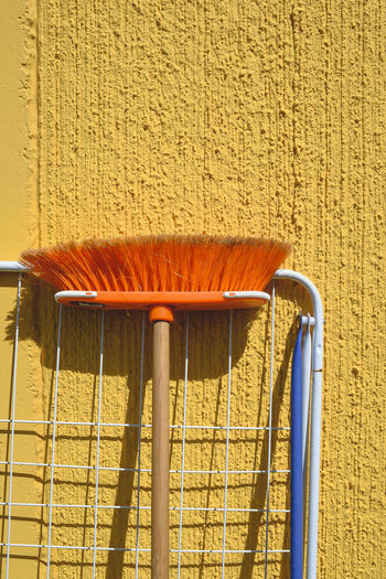 Cleaning Cleaning Equipment Sunny Yellow Flower Broom Built Structure Choice Clothes Rack Day Drying Rack Equipment Materials No People Outdoors Resting Still Life Summer Sunlight Vertical Wall Wall - Building Feature Yellow