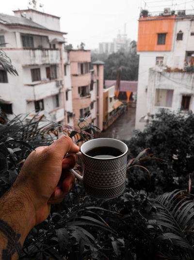 Cropped hand of man holding coffee cup outdoor
