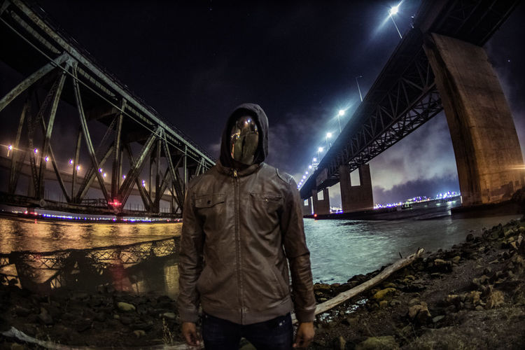 Man in mask standing against bridge at night