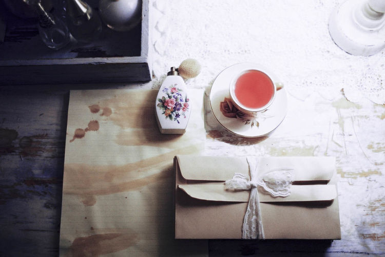 High angle view of tied up envelops with perfume sprayer and tea on table