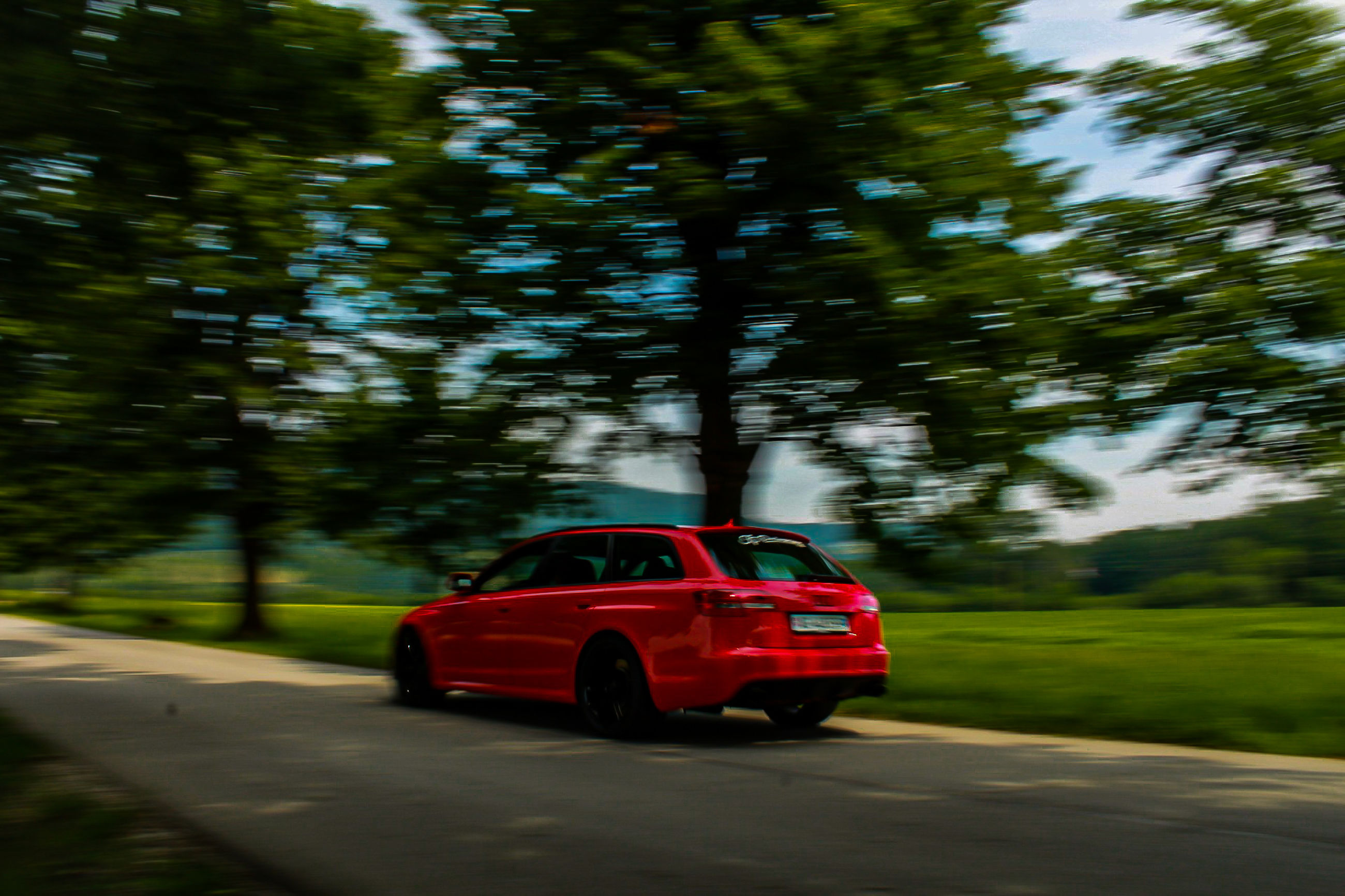 mode of transportation, transportation, car, motor vehicle, tree, land vehicle, red, blurred motion, plant, motion, nature, day, road, no people, green color, city, travel, outdoors, on the move, sunlight