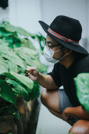 Side view of man examining leaf of plant