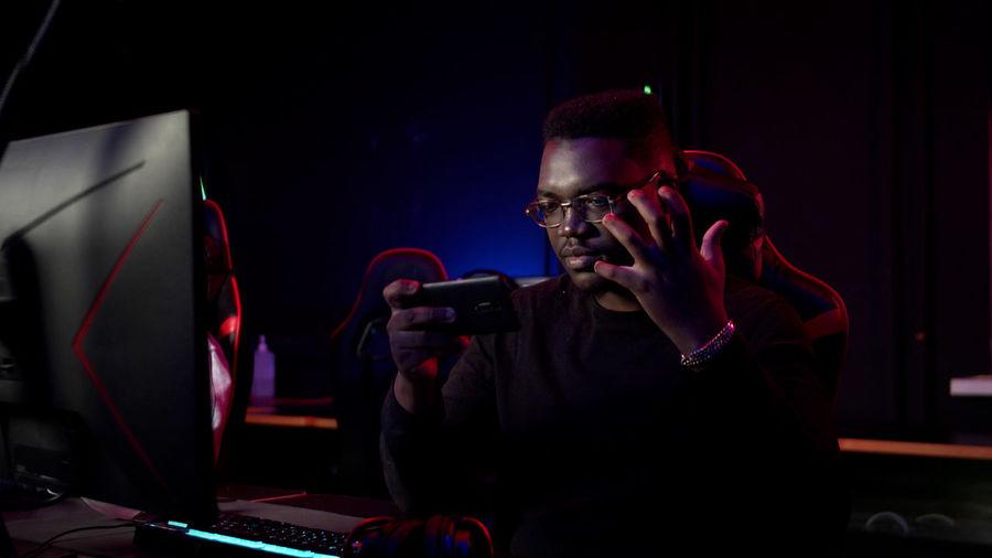 Man using mobile phone while sitting in darkroom