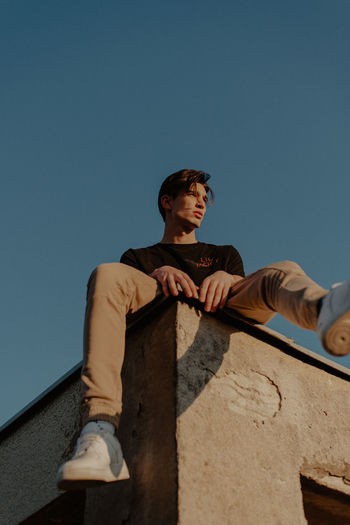 Low angle view of young man looking at camera against clear sky