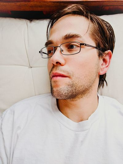 Man wearing eyeglasses looking away while sitting on sofa at home