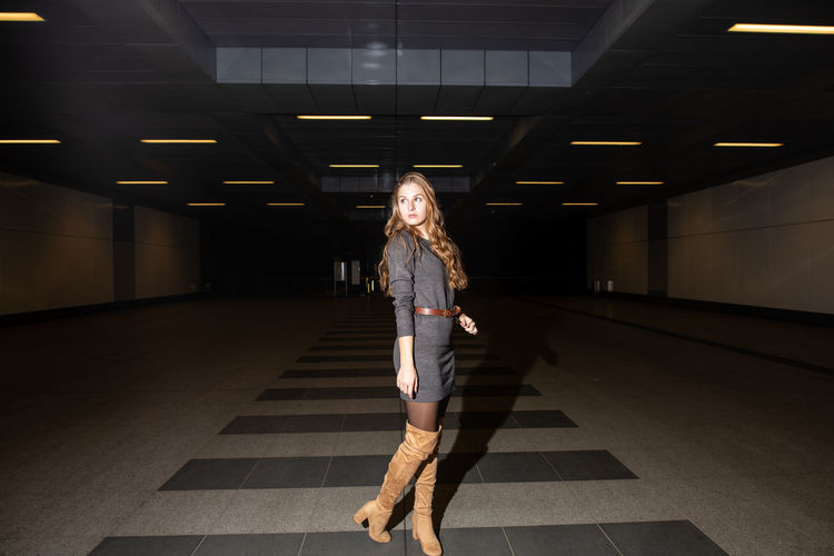 Full length of woman standing in underground walkway