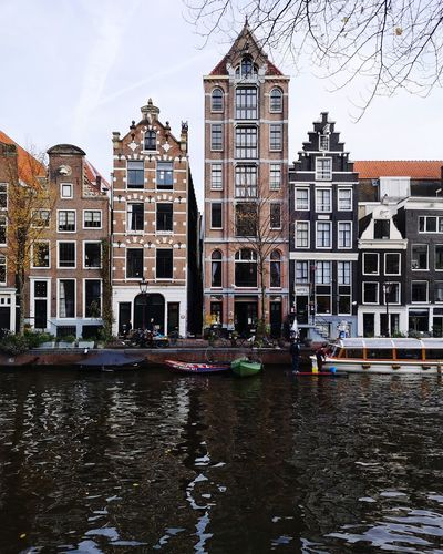Canal by buildings against sky in city