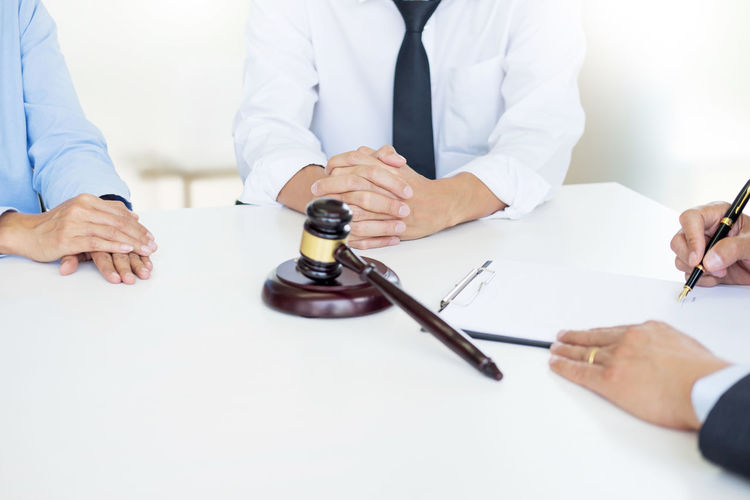 High angle view of couple with judge at desk
