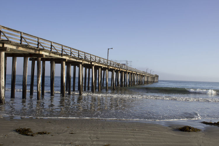 Pier Water Wave Sea Beach Sand Wooden Post Low Tide Water's Edge Pier Clear Sky Seascape Horizon Over Water