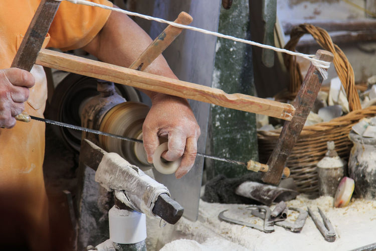 Midsection of craftsperson using hand saw on alabaster at workshop
