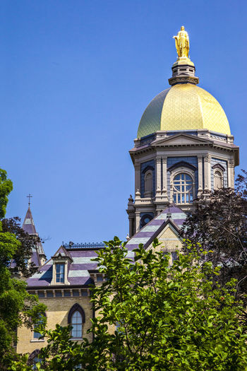 University of Notre Dame USA Blue Sky Religion Campus Culture Education Famous Knowledge Science And Technology Vertical Composition Christian Color Golden Tower Building Outdoor Sunny Day Tree Main Building Notre Dame Sculpture University Of Notre Dame USA