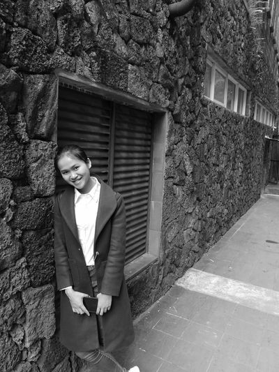 Portrait of smiling young woman leaning on wall while standing against window