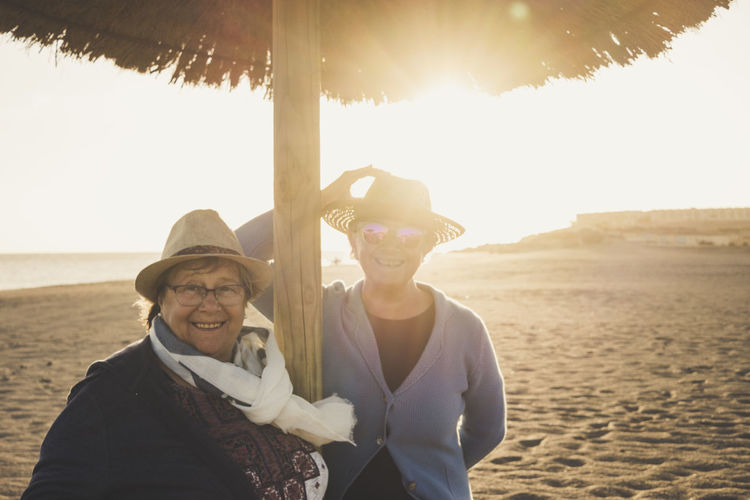 elderly couple of friends female with hats on the beach in winter time Backlight Beach Day Eyeglasses  Focus On Foreground Front View Happiness Lifestyles Looking At Camera Love Nature Outdoors Portrait Real People Sand Sea Sky Smiling Standing Sunlight Sunset Togetherness Two People Vacations Waist Up