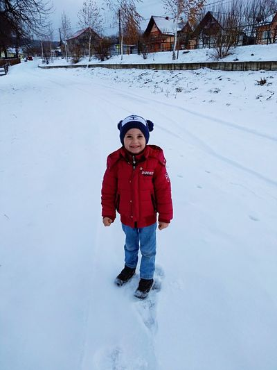 Portrait of cute boy standing on snow covered land