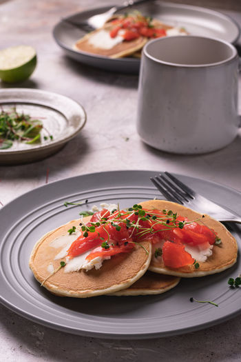 Morning breakfast with pancakes with salmon and micro greens on a gray plate