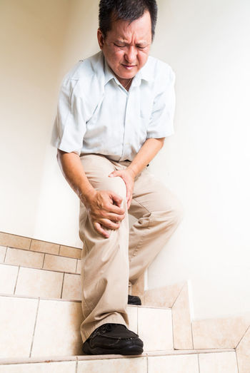 Asian middle age man with painful knee on steps and stairs Asian  Gout Paint the Town Yellow Adult Ageing Full Length Help Home Interior Indoors  Infection Inflammation Inflammed Knee Malaysian Men Middle Ages Steps And Staircases Suffering Tired