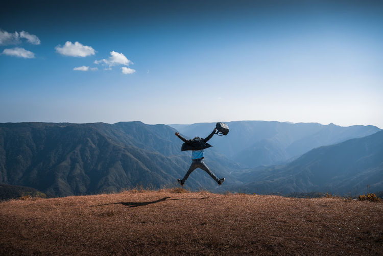Man jumping against mountains