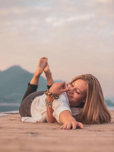 Portrait of woman lying down against sky