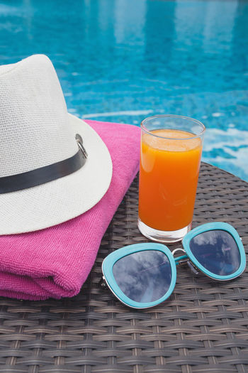 High angle view of personal accessories with drink on table by poolside