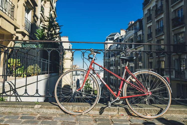 Bicycles parked by railing against buildings in city