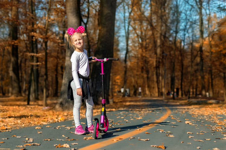 Full length portrait of smiling girl with push scooter standing against trees during autumn
