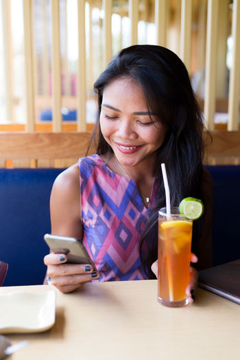 Young Woman Using Phone In Restaurant
