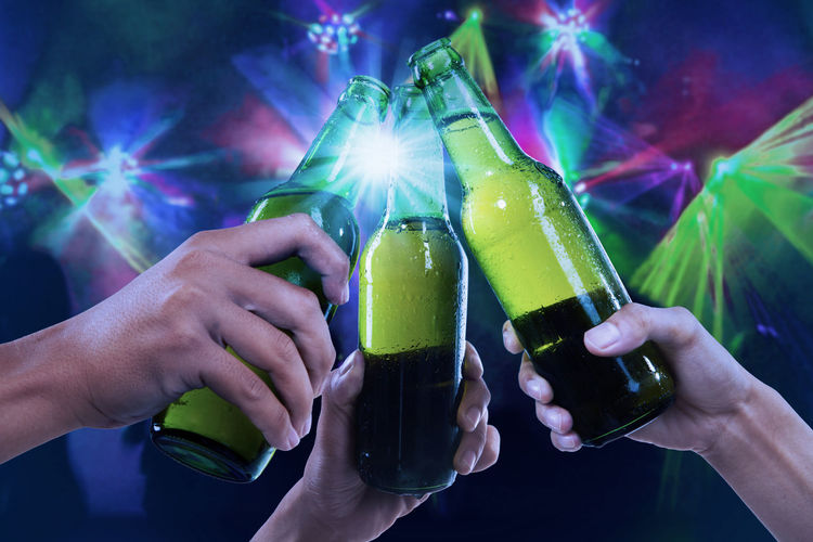 Close-Up Of Hands Toasting Beer Bottles Against Illuminated Lights