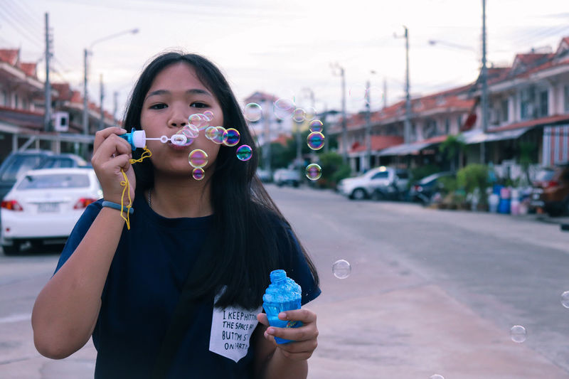 Portrait of girl blowing bubbles on road against sky