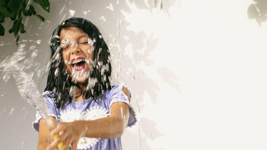 Girl standing splashing against wall