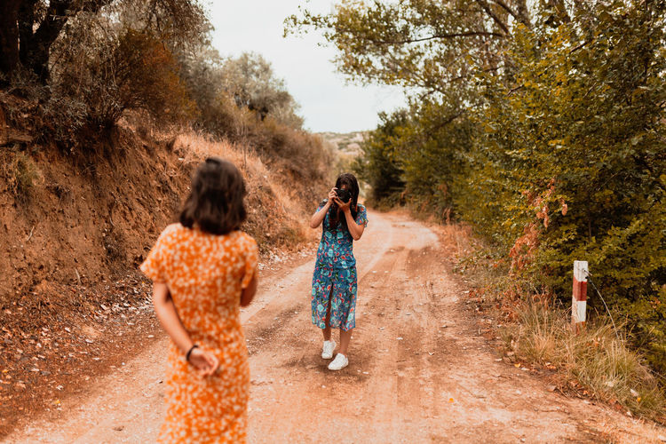 Woman photographing girlfriend while standing on dirt road in forest