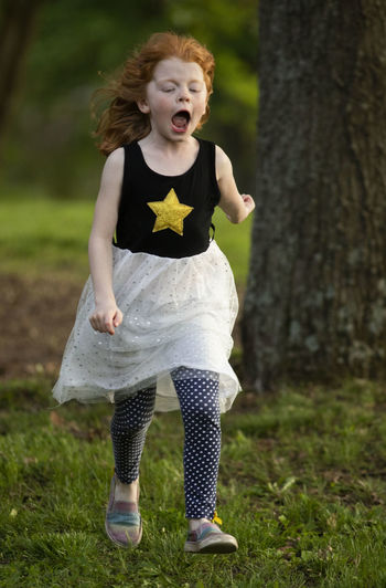 A five-year-old girl is running in her yard in evening light while yelling with joy. Childhood Plant Full Length Child One Person Land Real People Women Leisure Activity Girls Front View Tree Grass Field Lifestyles Innocence Focus On Foreground Outdoors Hairstyle Running Girl Outside Rural Scene Rural Rural America Fun Scream Screaming Roar Star Dress Polka Dot Red Hair Activity Eyes Closed  Peak Action Joy Joyful Evening Light Tree Grass Yard