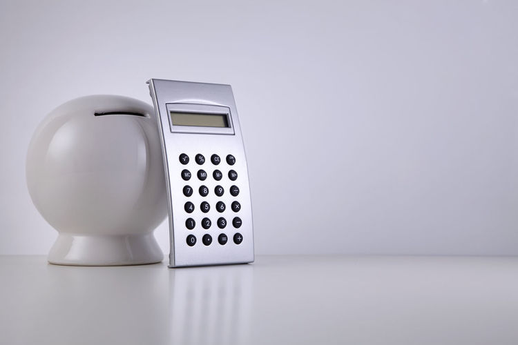 Close-up of piggy bank and calculator on table against white background