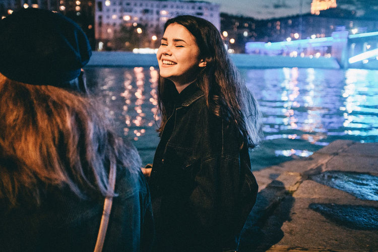 Beautiful woman smiling while standing in water at night