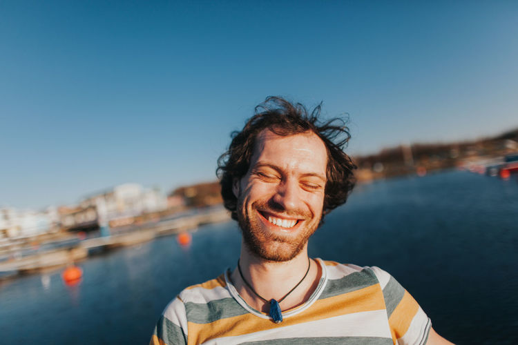 portrait of cheerful caucasian man smiling Happiness Joyful Laughing Adult Carefree Casual Clothing Cheerful Emotion Enjoyment Front View Hairstyle Happiness Headshot Joy Nature One Person Outdoors Portrait Positive Emotion Sky Smiling Teeth Toothy Smile Water Young Adult This Is Natural Beauty Moments Of Happiness
