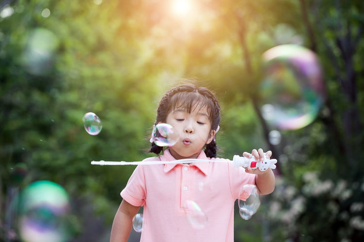 Portrait of funny asian little girl is blowing soap bubbles Blowing Bubble Bubble Wand Child Childhood Day Focus On Foreground Fragility Front View Headshot Innocence Mid-air Nature Offspring One Person Outdoors Plant Portrait Standing Sunlight Vulnerability