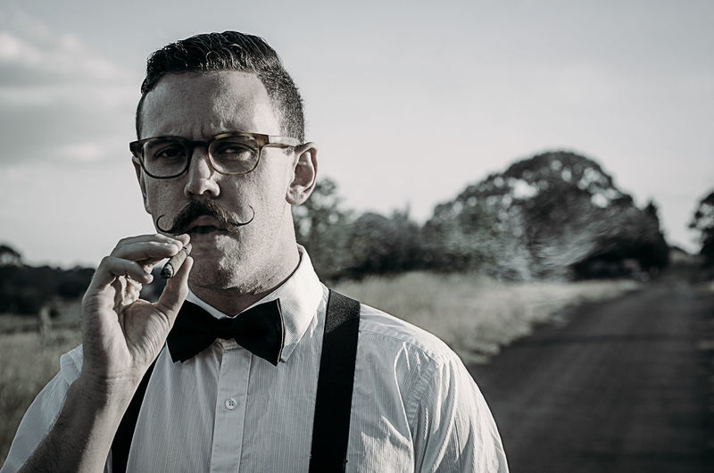 During the month of November, men grow their moustache long in the name of charity. The term is Movember. Here is a good friend of mine who modelled as I took this image in rural Australia. Australia Nikon Smoking Beard Bow Tie Day Facial Hair Focus On Foreground Front View Glasses Headshot Leisure Activity Lifestyles Looking At Camera Males  Mature Men Men One Person Outdoors Portrait Real People Sky Week On Eyeem Young Adult Young Men A New Perspective On Life Capture Tomorrow