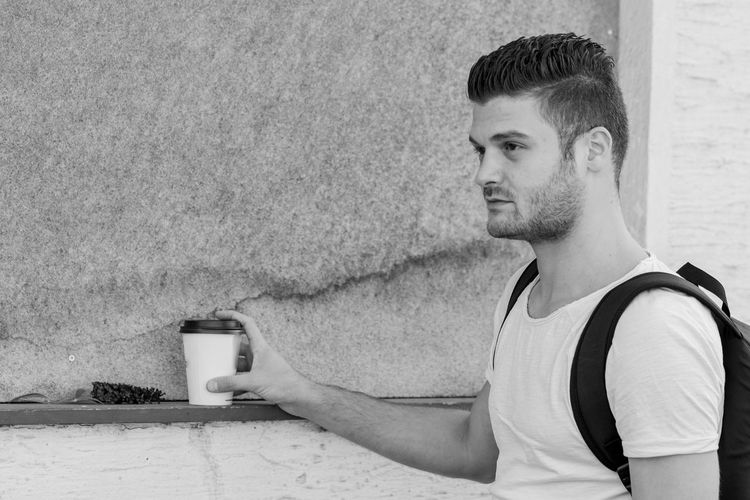 Portrait of young man drinking against wall