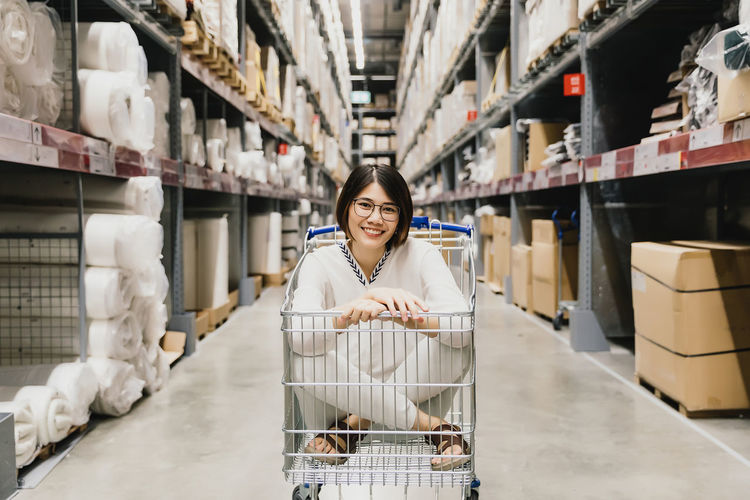 Portrait of smiling woman sitting in trolley at warehouse