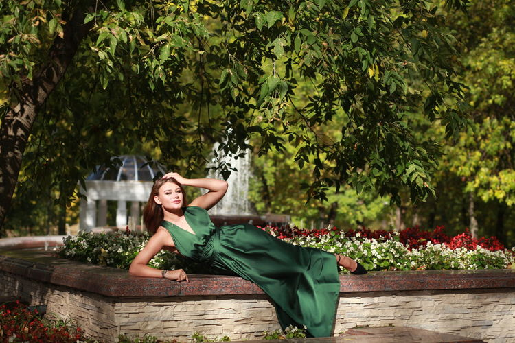 Portrait of woman sitting by tree against autumn park background, wearing green silk dress